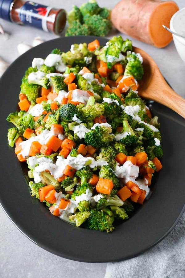 Plate with sautéed broccoli and sweet potatoes, topped with creamy garlic ranch with dill