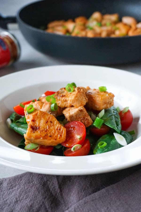 Plate with spicy salmon with leafy green salad and tomatoes.
