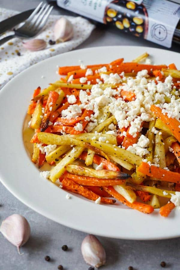 White round ceramic plate with roasted in olive oil, salt and ground black pepper carrots and parsnips topped with crumbled white cheese.