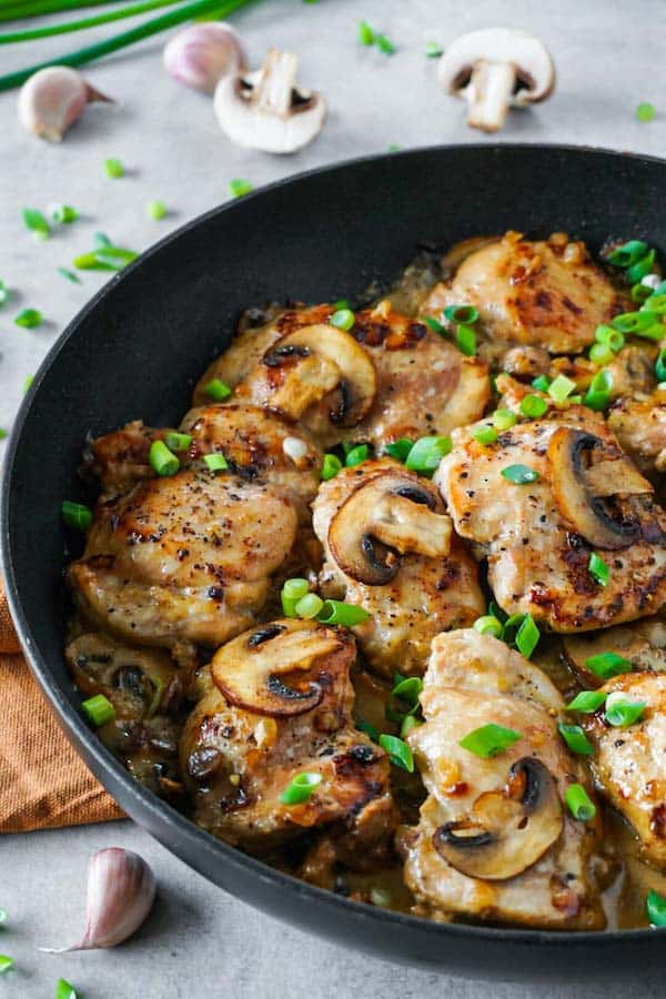 Close up of a black skillet with fried chicken thighs with creamy mushroom sauce garnished with chopped green onions.