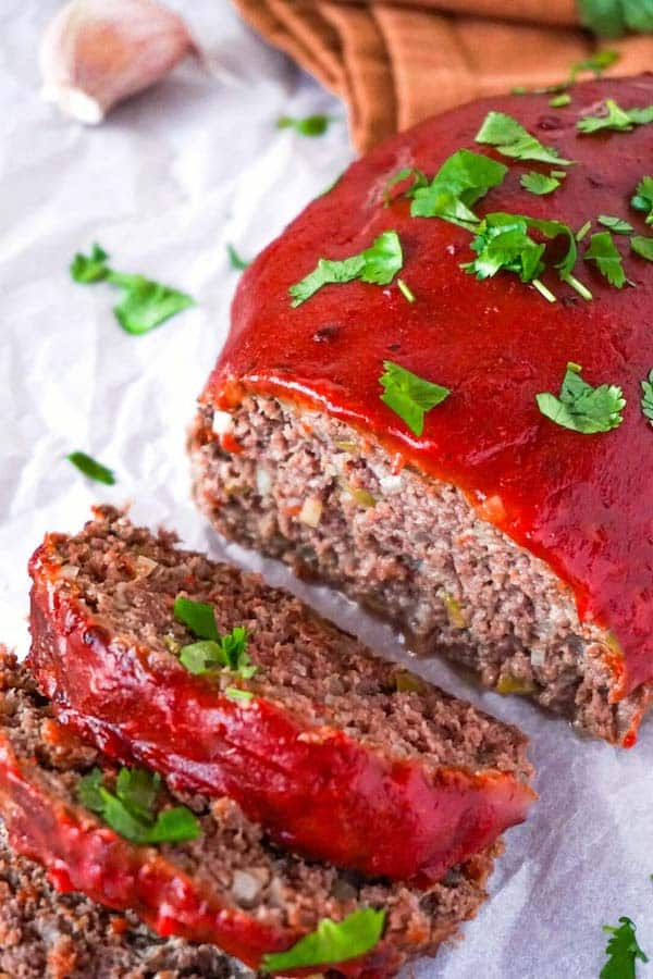 Close up picture of sliced meatloaf with onions garlic and green olives covered with tomato glaze and garnished with chopped cilantro.
