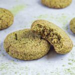 Two green tea cookies lying on a grey cooking surface, one bite taken from one of the cookies.