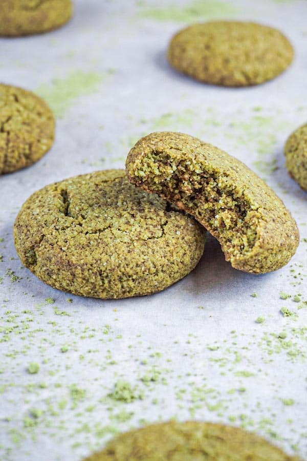 Close up picture of two green tea cookies lying on a grey cooking surface, one bite taken from one of the cookies.