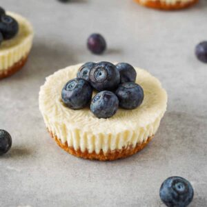 Close up picture of a mini cheesecake topped with fresh blueberries on a grey working surface with berries lying around.