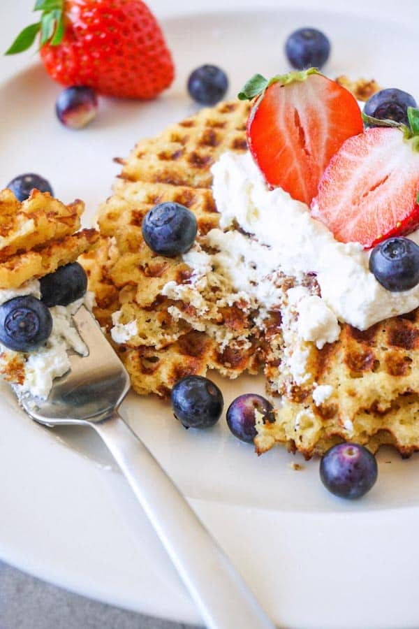 Close up picture of gluten-free waffles topped with whipped cream, fresh blueberries and strawberries on a white plate, one bite taken.