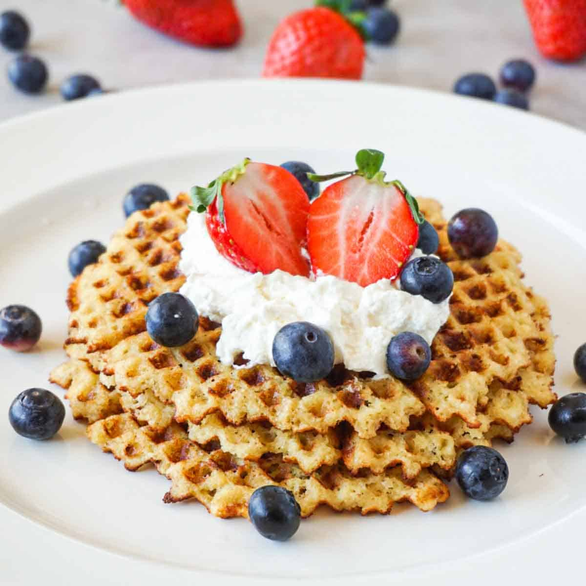 Keto waffles topped with whipped cream, fresh blueberries and strawberries on a white ceramic plate.