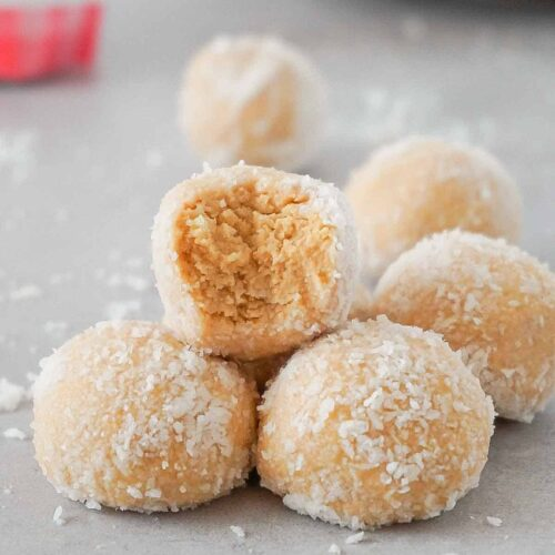 Pyramid of keto peanut butter balls covered with coconut flakes on a grey cooking surface, one bite is taken from the top one.
