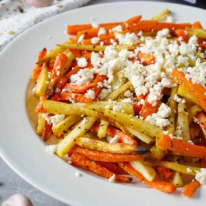 Close up shot of a white plate with roasted parsnips and carrots topped with crumbled white cheese.