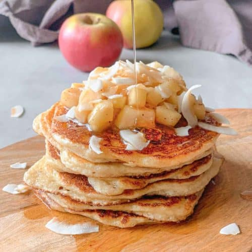Tower of cottage cheese pancakes topped with fresh apple, toasted coconut flakes and maple syrup on a wooden board.