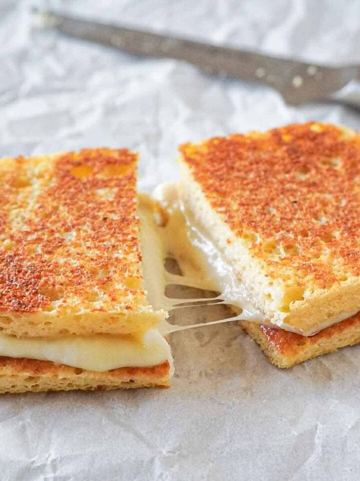 Gluten-free and low carb grilled cheese sandwich cutter in half with stringy mozzarella and gouda cheese.