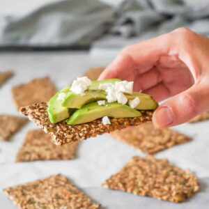 A hand holding homemade seed cracker with some avocado and white cheese on top, more keto seed crackers on the background.