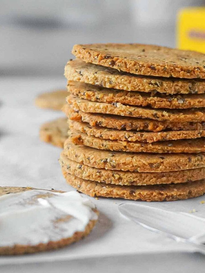 Tower of keto crackers with chia seeds on a parchment paper.