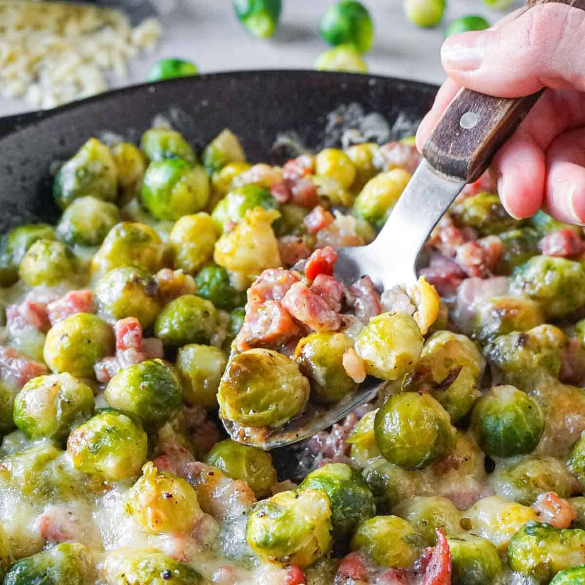 Cast iron skillet full of cheesy brussels sprouts with bacon with a silver spoon digging in.