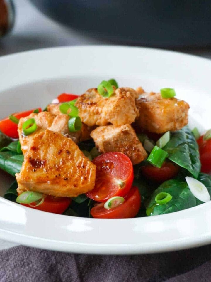 Spicy salmon bites with fresh vegetable salad garnished with chopped green onions.