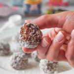 A hand holding brownie bliss ball covered in coconut flakes, one bite taken.