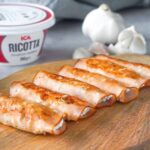Turkey roll ups with ricotta cheese and garlic on the wooden board.