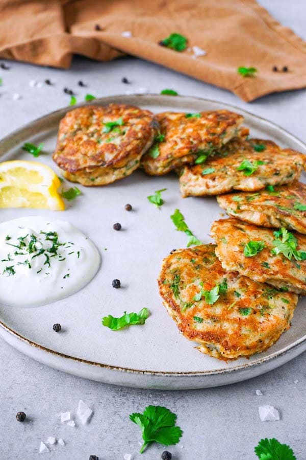 Keto salmon cakes garnished with chopped cilantro on a large ceramic beige plate, served with some sour cream and lemon slices.