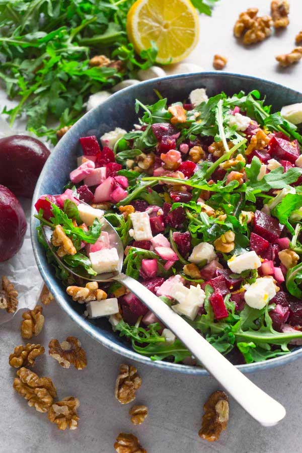 A blue salad bowl filled with red beet salad with arugula, walnuts and feta cheese, a silver spoon with some salad lying in the bowl.