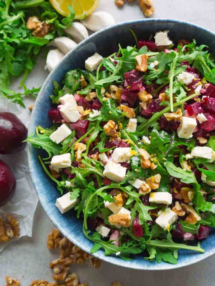 Top down picture of a blue ceramic bowl full of arugula red beet salad with feta and walnuts on a grey working top, whole beets, garlic, arugula leaves, walnuts are lying around.