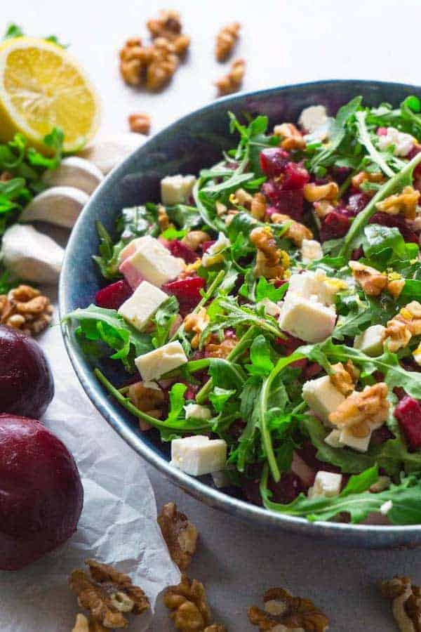 Close up shot of a beetroot salad with feta cheese, walnuts and arugula in a blue ceramic bowl, beets, lemon, garlic and walnuts are lying around.