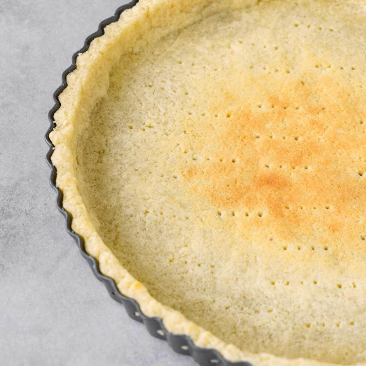 Close up picture of partially blind baked keto pie crust, the base pricked with a fork, in a tart pan lying on a grey working surface.