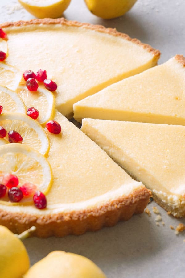 Freshly baked and partially sliced custard tart decorated with thinly sliced lemons and pomegranate on a grey kitchen top, fresh lemons are lying around.
