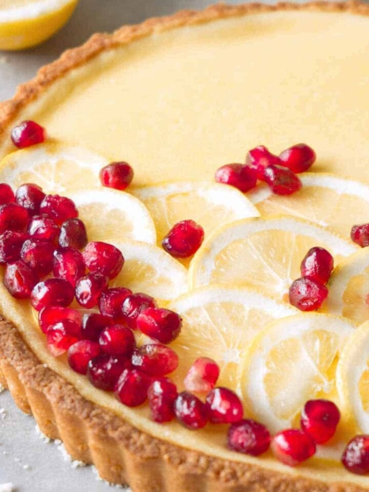 Close up shot of a sliced gluten-free custard tart decorated with slices of lemon and pomegranate.