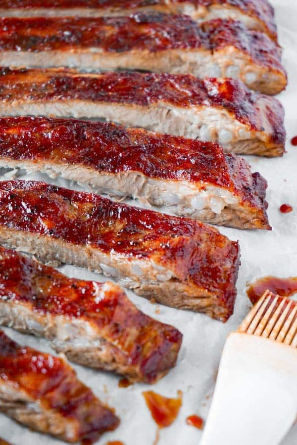 Freshly baked and sliced spare ribs glazed with keto bbq sauce, a brush with sauce on it is lying on the right side.