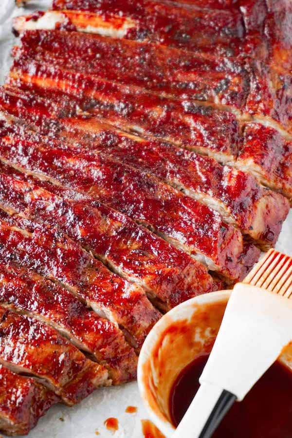 Sliced pork spare ribs glazed with sugar-free bbq sauce lying on a white parchment paper, brush with bbq sauce on the right side.