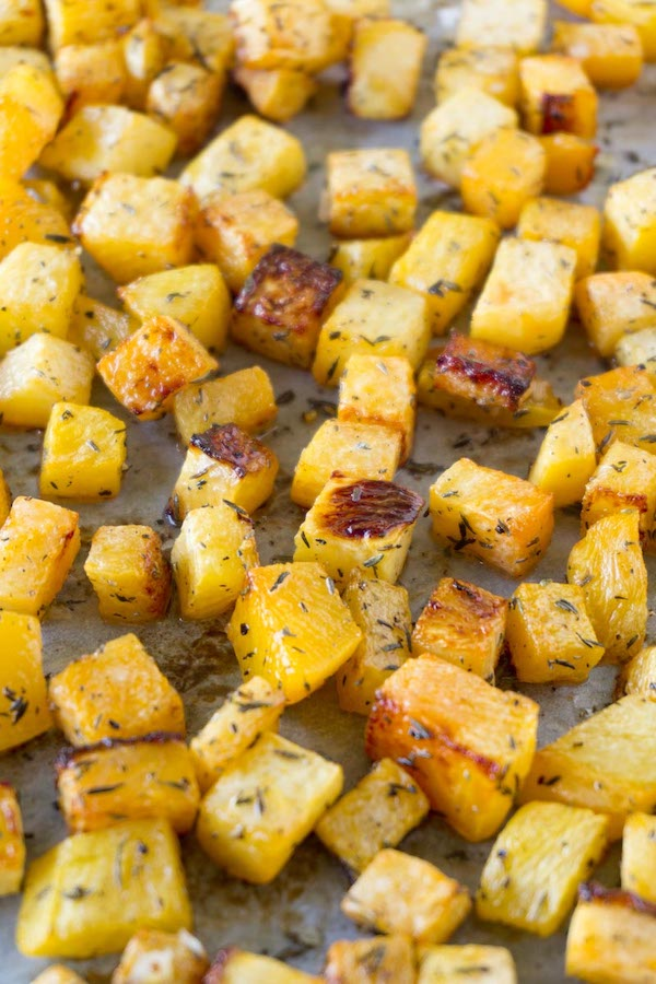 Roasted with olive oil and thyme rutabaga cubes on a baking tray .