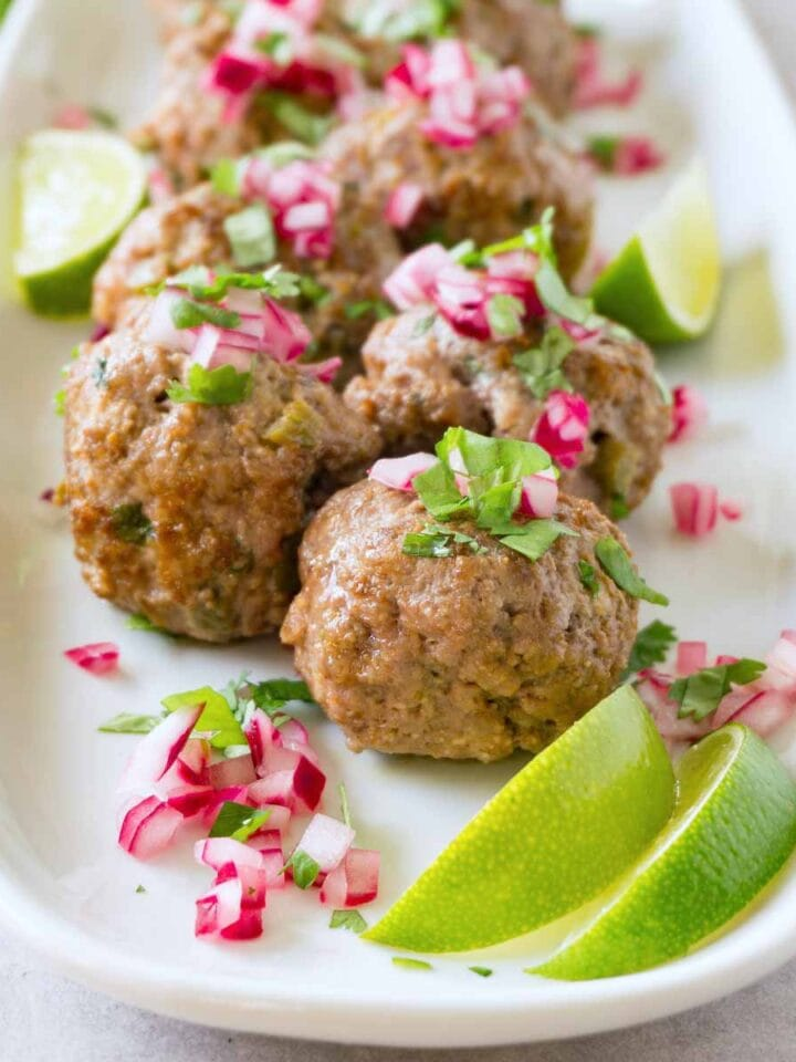 Close up shot of keto meatballs garnished with pickled red onions and chopped cilantro served on a white plate with lime wedges.