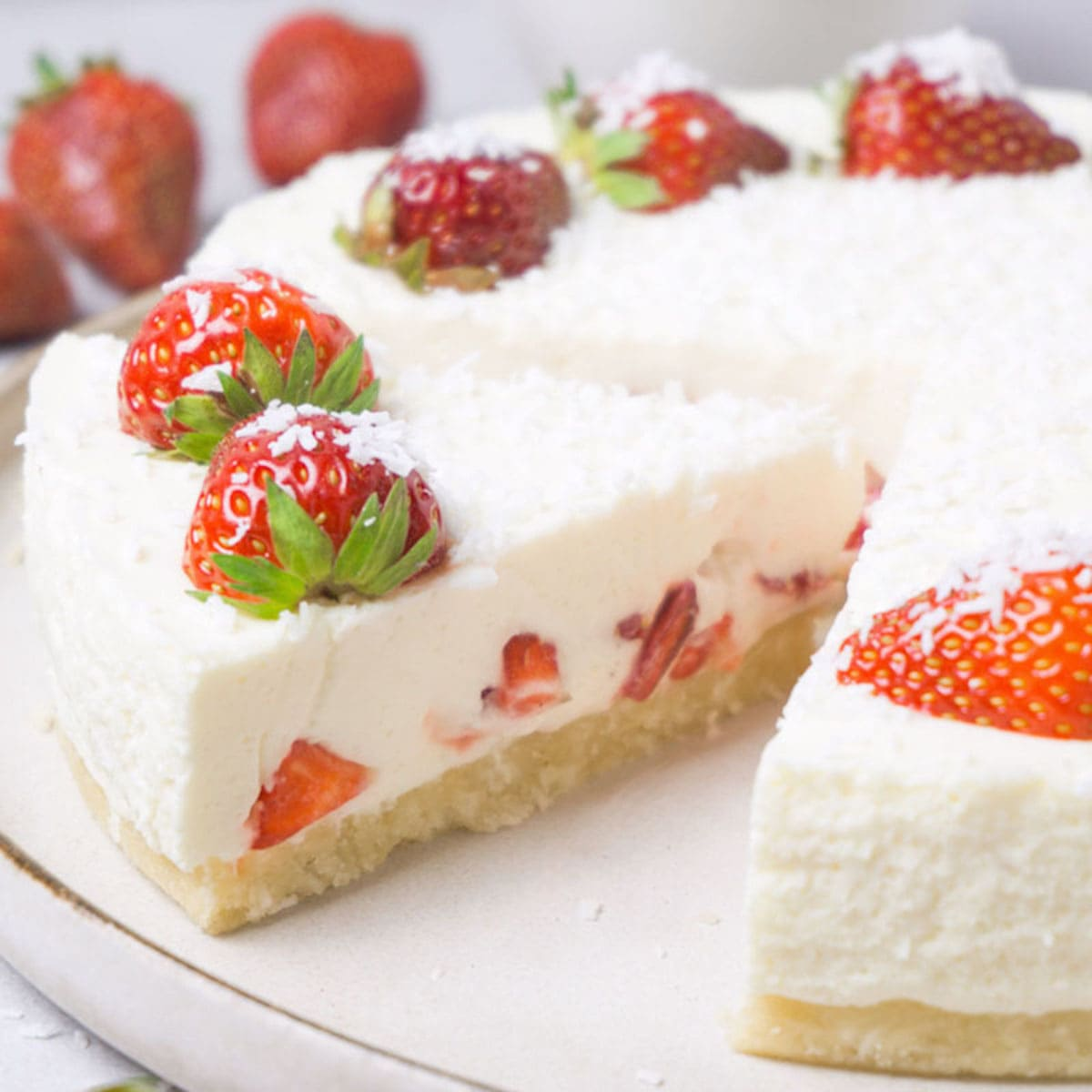 Close up shot of a sliced strawberry cheesecake decorated with fresh strawberries.