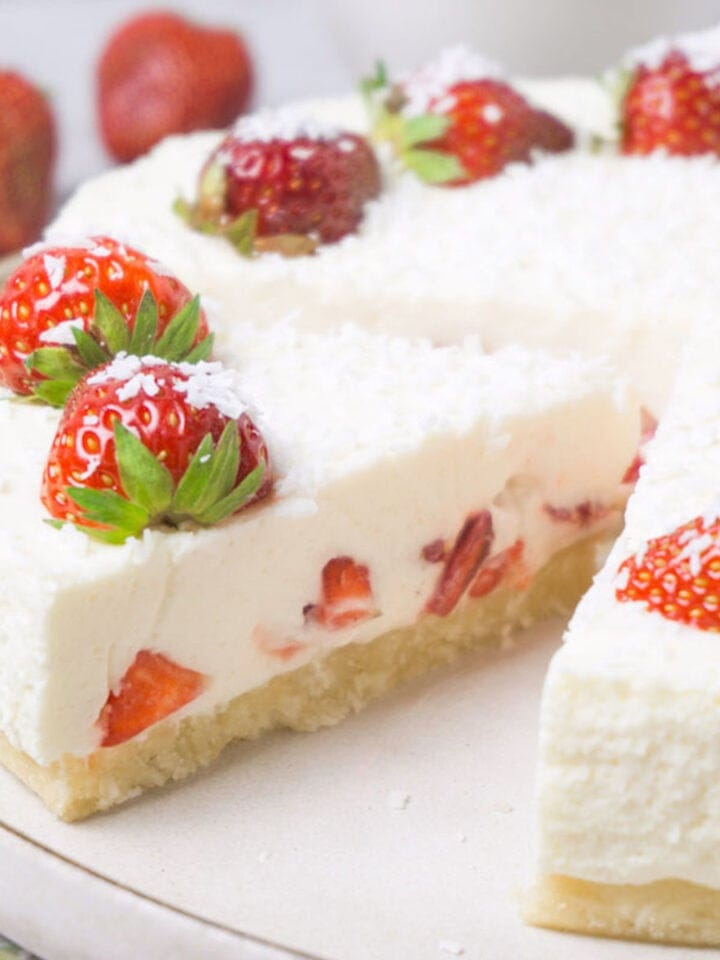 Close up shot of a sliced strawberry cheesecake topped with fresh berries and shredded coconut.