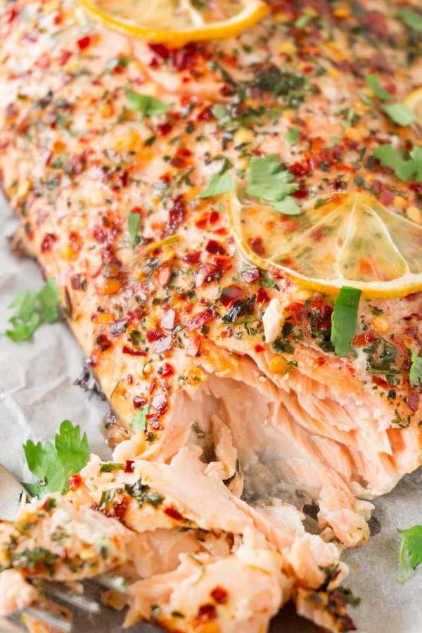 Freshly baked keto salmon with cilantro, chili flakes and lemon slices, small piece is taken.
