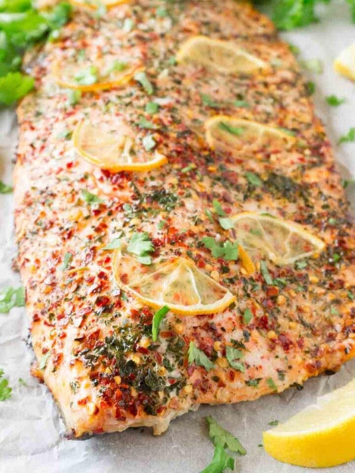 Oven-baked salmon fillet with cilantro, chili flakes and lemon slices on a baking tray lined with white parchment paper, chopped fresh cilantro and lemon wedges are lying around.