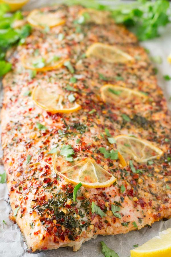 salmon fillet with cilantro, chili flakes and lemon slices, garnished with fresh cilantro served with lemon wedges on a baking tray lined with white parchment paper.
