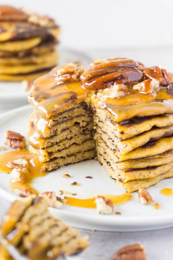 Sliced tower of gluten-free pumpkin pancakes with caramel sauce and pecans on a light blue plate.