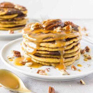 Close up shot of a tower of pumpkin pancakes with caramel sauce and pecans.