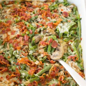 Close up shot of low carb green bean casserole dish topped with crispy bits of bacon, a silver spoon full of green beans lying inside the dish.