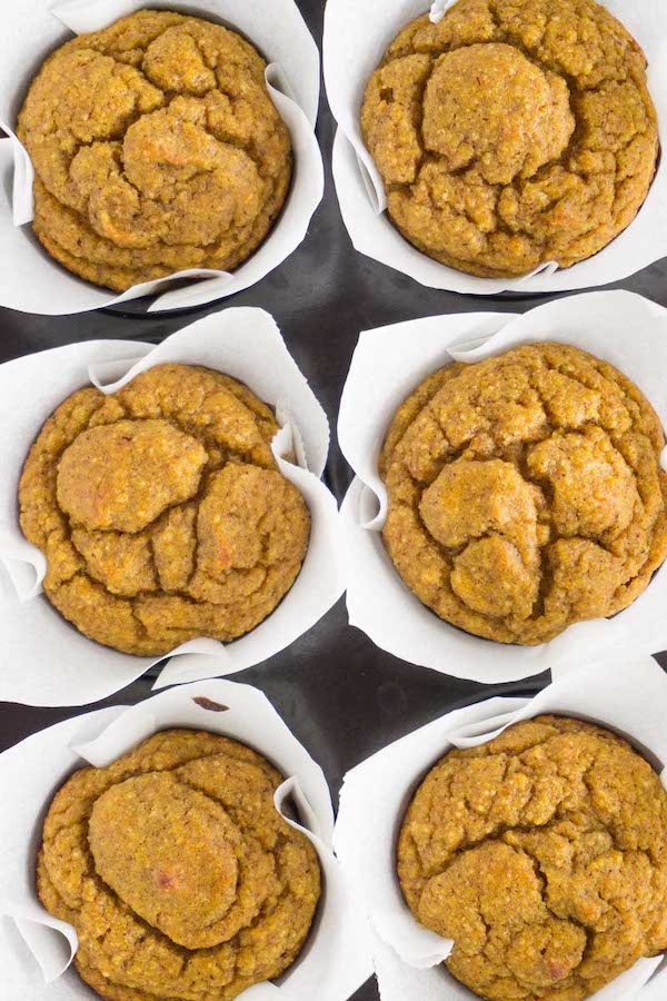 6 freshly baked gluten-free pumpkin muffins in a black muffin pan, view from above.