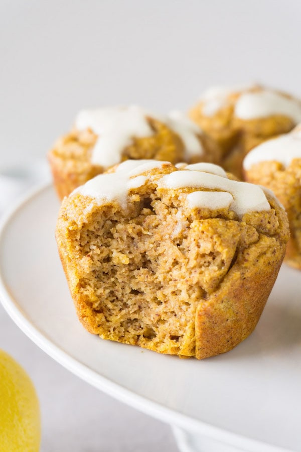 Pumpkin muffins topped with sugar-free glazing on a footed white cake platter, one bite taken from one of the muffins.