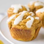 Close up shot of a pumpkin muffin with white sugar-free glaze on top.