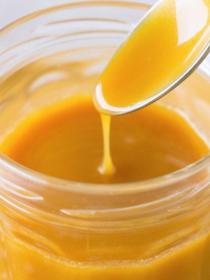 Close up shot of a caramel sauce in a glass gar, a silver spoon scooping out the caramel.