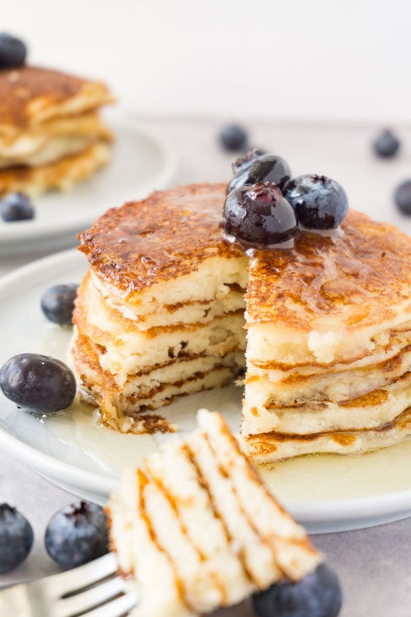 Keto cottage cheese pancake tower topped with fresh blueberries and sugar-free syrup on a small round plate, one piece taken.