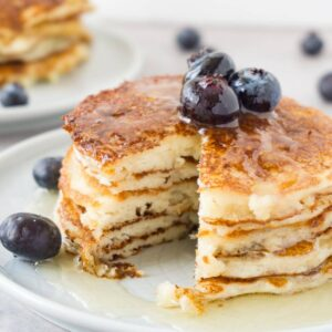 Close up image of cottage cheese pancake tower topped with fresh blueberries and sugar-free syrup, one piece taken.
