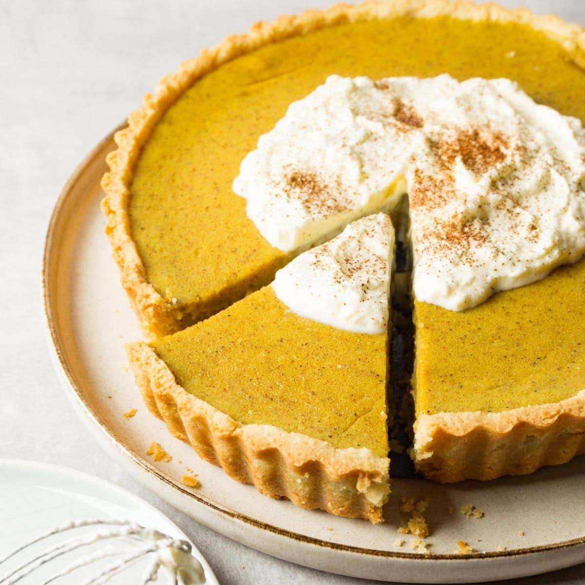 Close up image of a pumpkin pie with whipped cream and ground cinnamon on top served on a large round plate, one piece cut out but not taken.