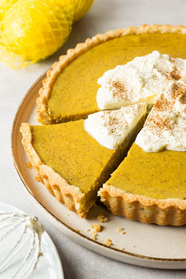 Sugar-free pumpkin pie topped with whipped cream and ground cinnamon on a large round plate, one piece cut out but not taken.