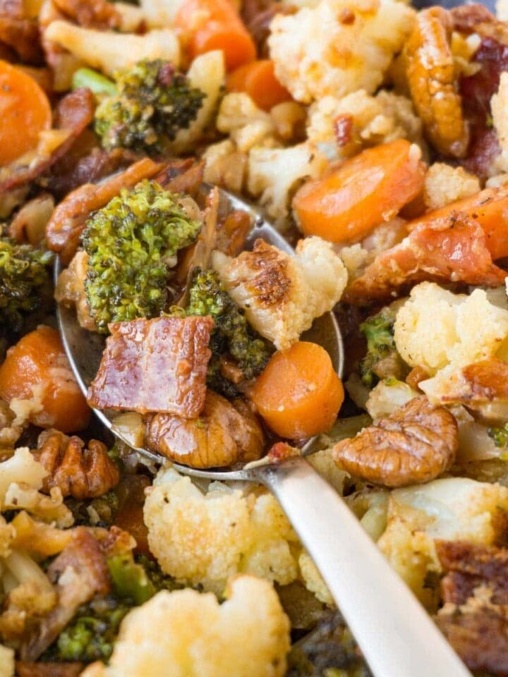 Close up image of a bowl with stuffing with cauliflower, broccoli, carrots, bacon bits and pecan nuts, a spoon with stuffing in the bowl.