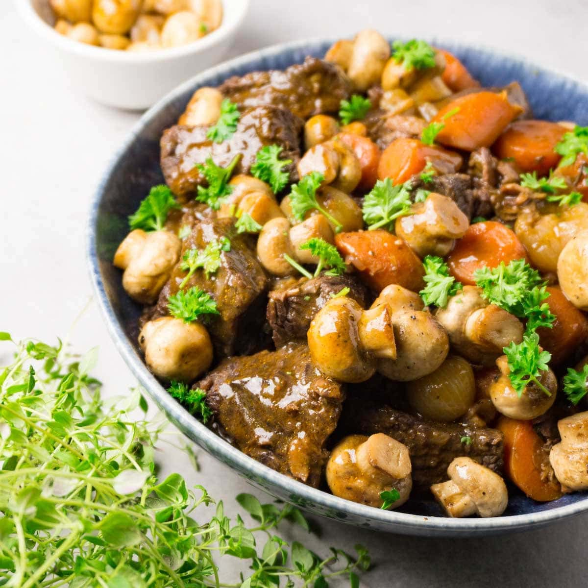 A round bowl with beef Burgundy garnished with fresh parsley.
