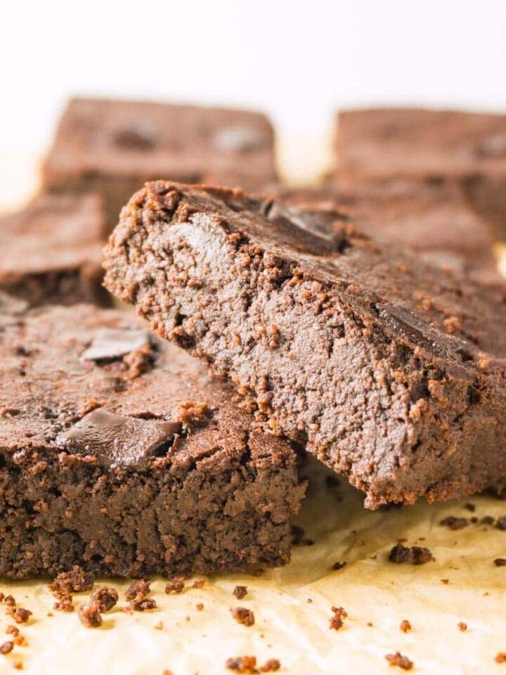 Close up image of fudge brownies on a brown parchment paper, more brownies on the background.